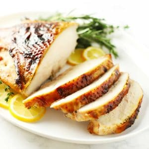 Roasted turkey breast on white platter.