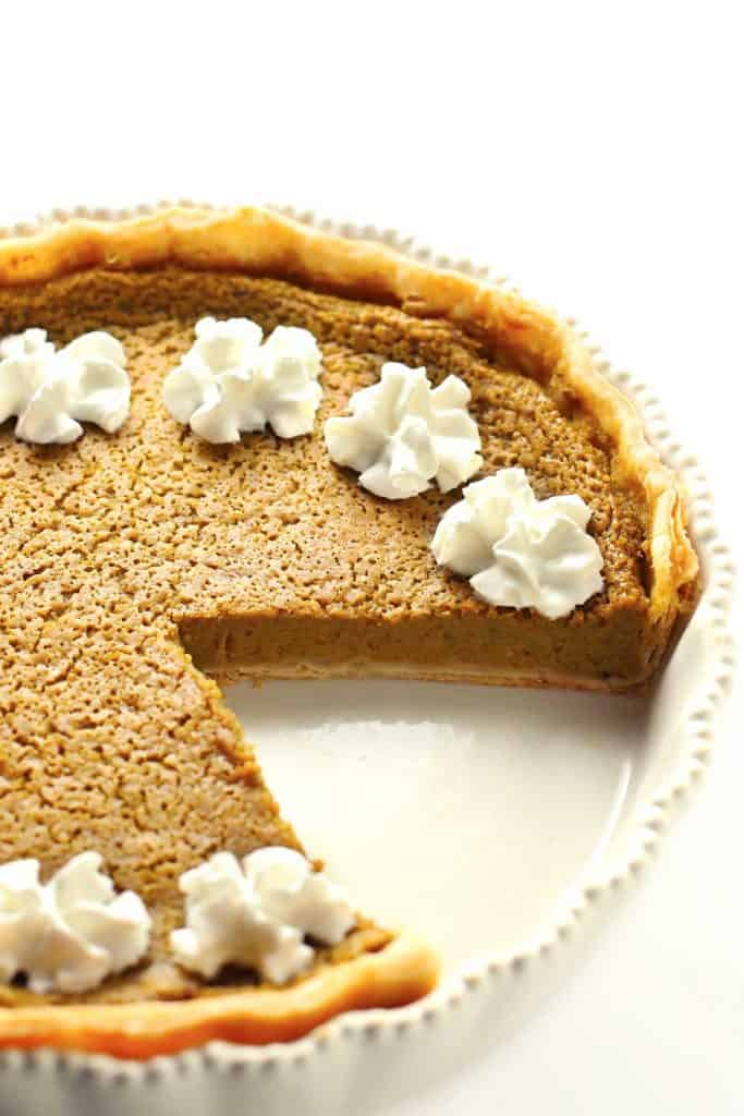 Pumpkin pie in white dish with whipped cream.
