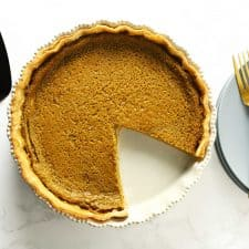 Easy pumpkin pie next to serving spatula, plates and forks.