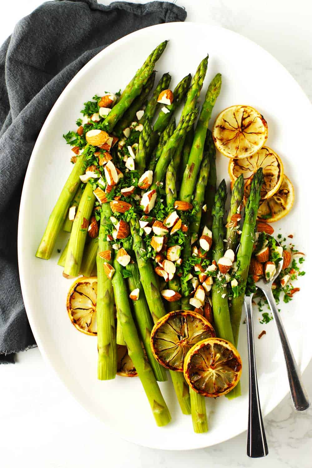 Baked asparagus on white platter with lemon and almonds.