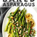 Asparagus on white platter with herbs, nuts and lemon slices.