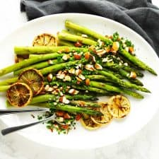 Baked asparagus on white platter with almonds and lemon.