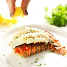 Squeezing lemon on baked lobster tail.