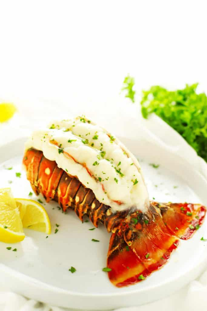 Butterflied baked lobster tail with lemon.