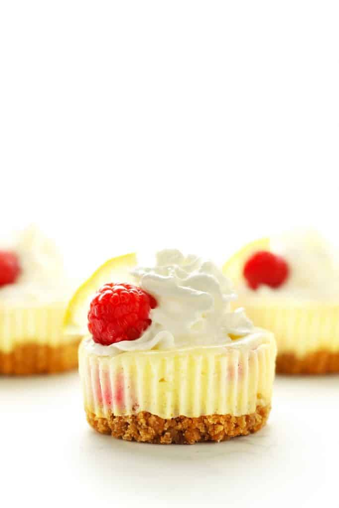 Mini cheesecake with whipped cream and a raspberry.