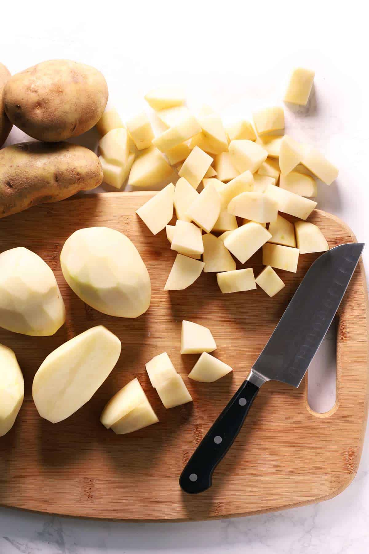 Peeled and cubed russet potatoes on cutting board with knife.