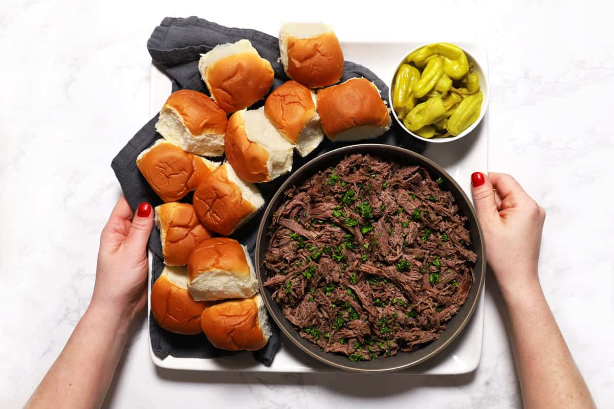 Two hands holding a tray of shredded Italian beef, buns and pepperoncini peppers.