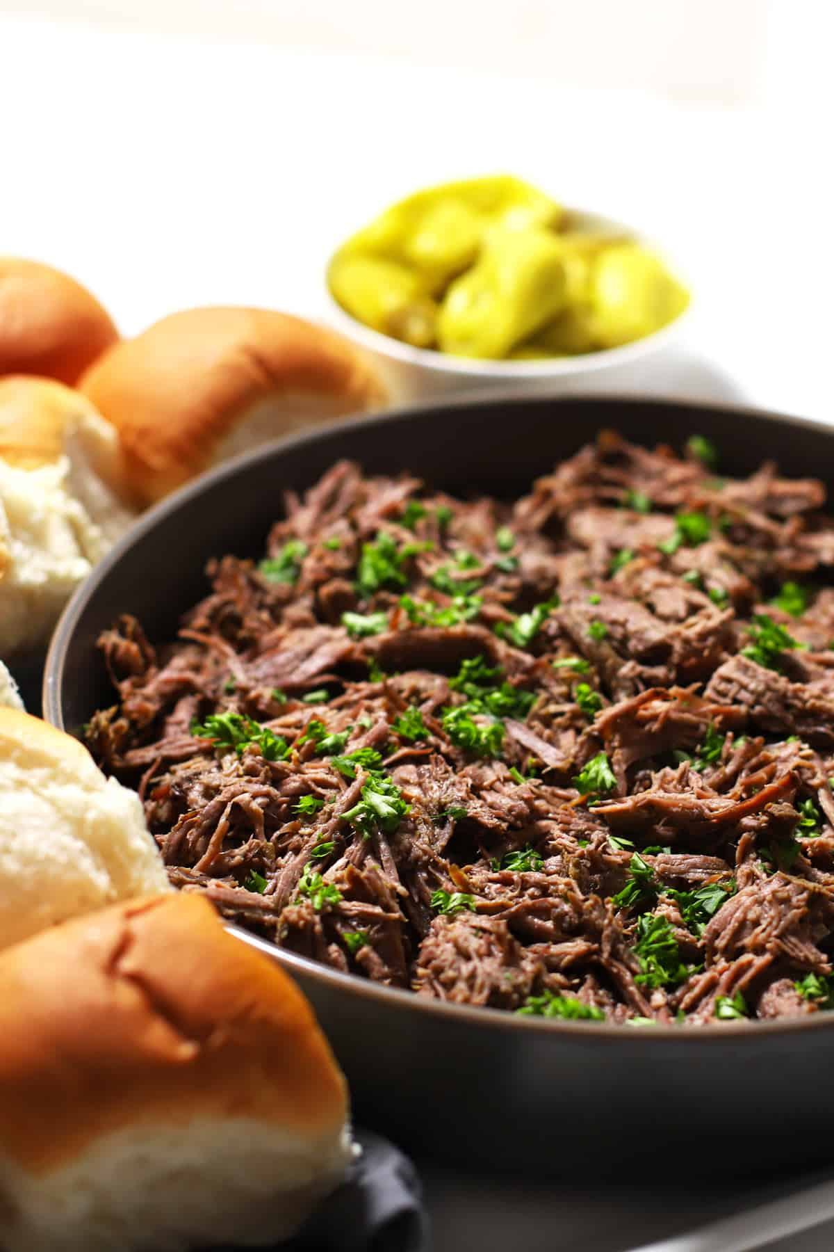 Shredded Italian beef on grey bowl on a platter with rolls.