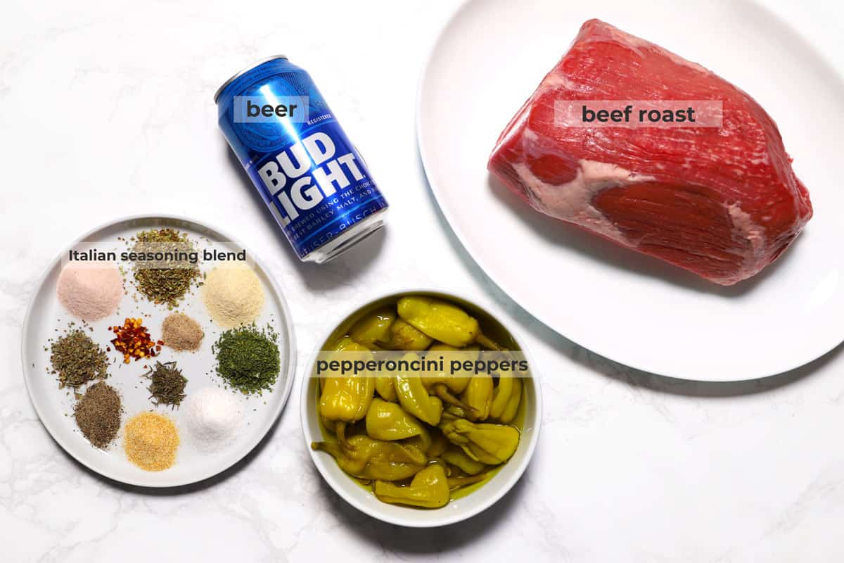 Beef roast, pepperoncini peppers, can of beer and spices to make Italian seasoning blend on a marble surface.
