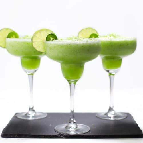 Three frozen margaritas with lime and jalapeno slices.
