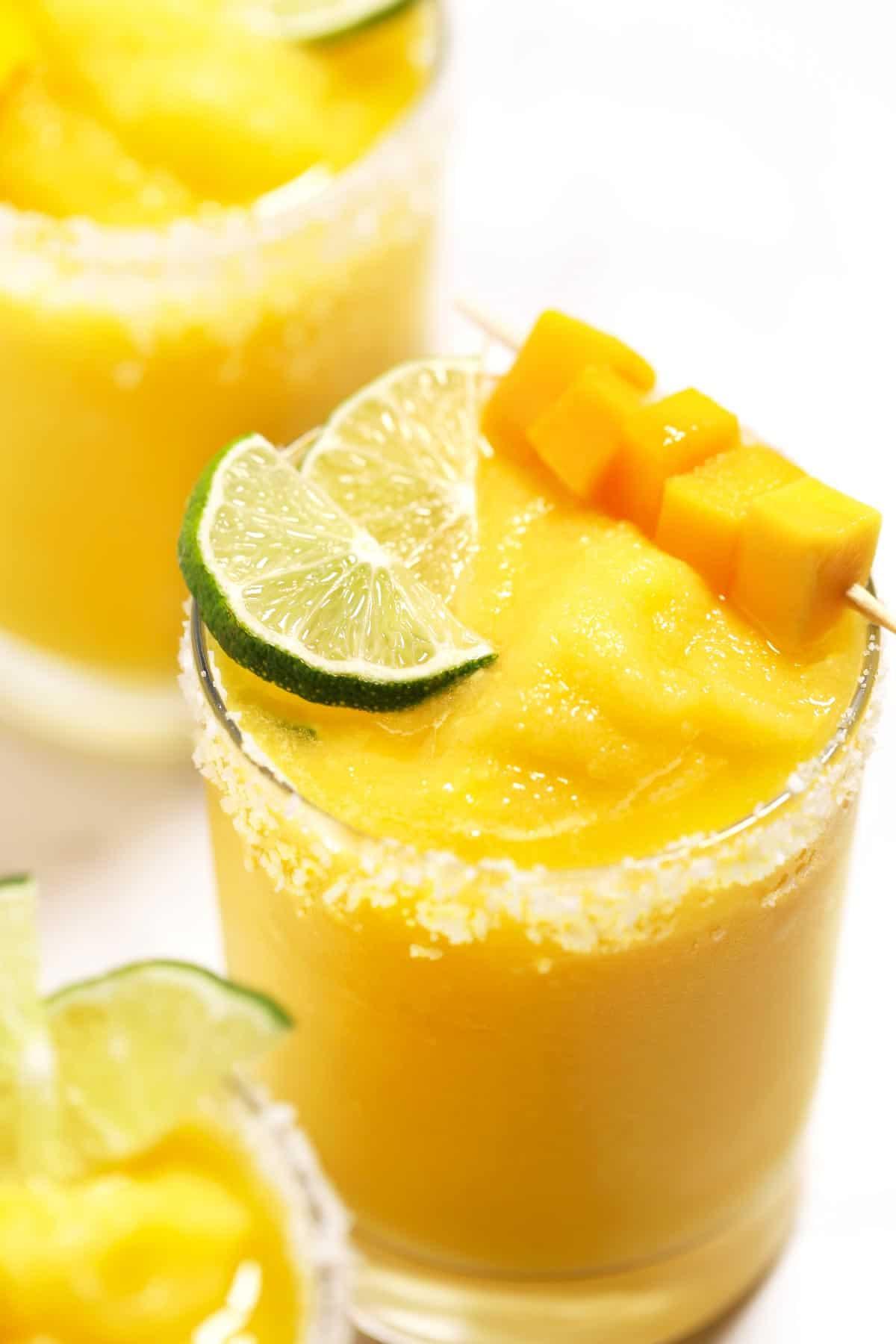 Mango margaritas garnished with lime, salt, and fresh mango.