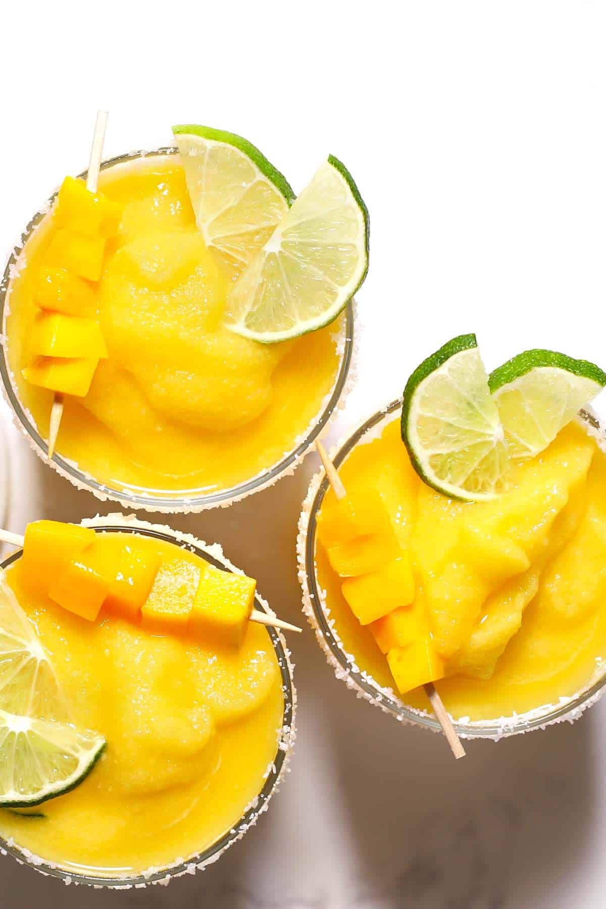 Frozen mango margaritas garnished with lime and fresh mango.