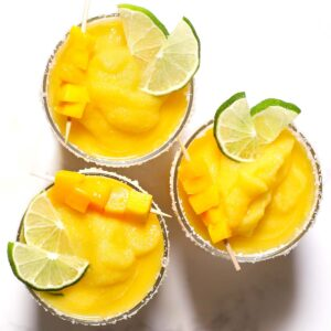 Three mango margaritas with lime.