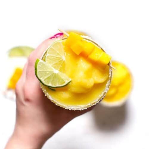 A hand holding a frozen mango margarita.