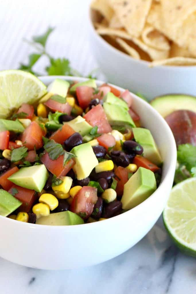 Black beans, corn, tomato and avocado in white bowl.