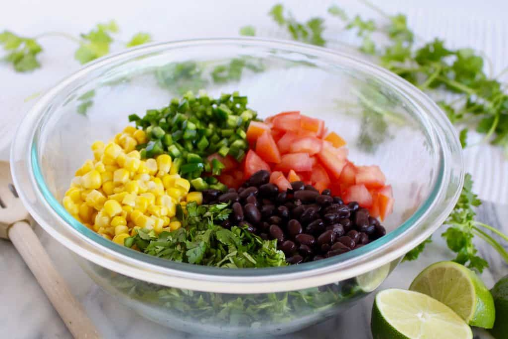 Black beans, corn, tomato and herbs in glass bowl.