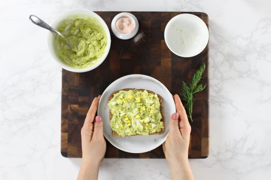 Avocado egg salad toast on white plate.