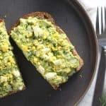 Avocado egg salad toast on grey plate.