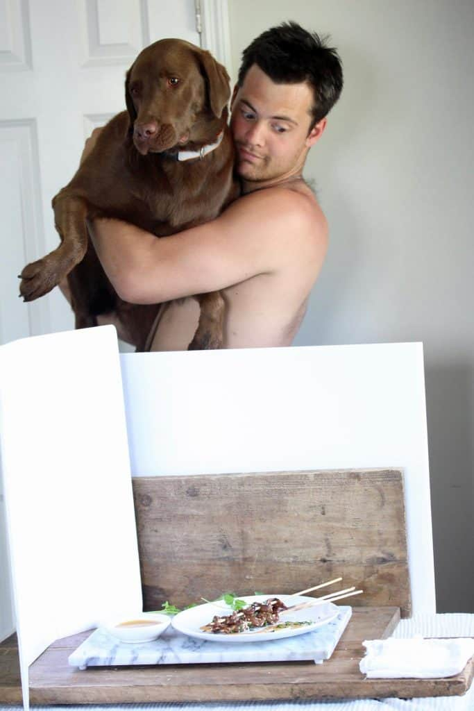 Man and chocolate lab looking at plate of food.