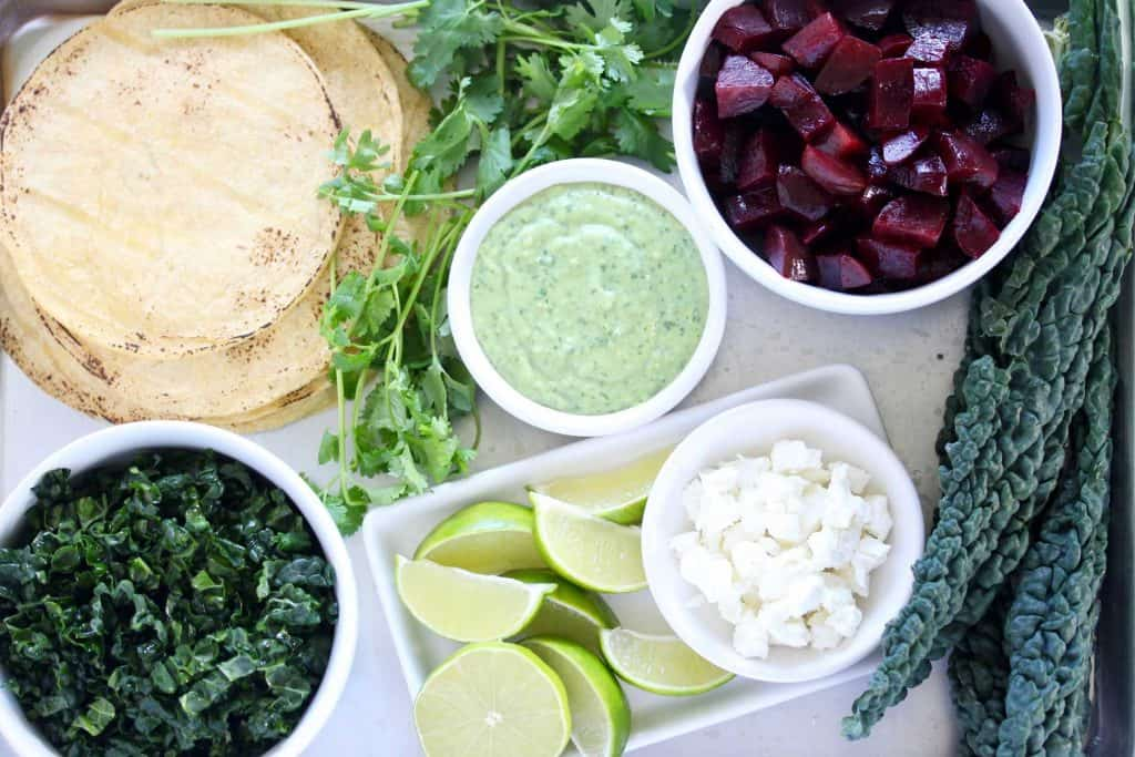 Beet and kale taco ingredients on white surface.