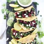 Beet and kale tacos on dark grey serving platter.