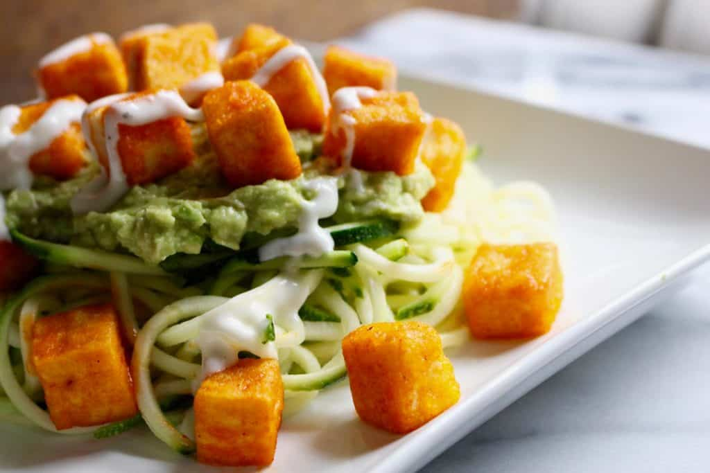 Tofu and zucchini noodles on white plate.