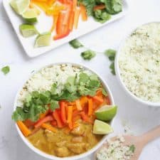 Curry, vegetables and rice in white bowl on marble surface.