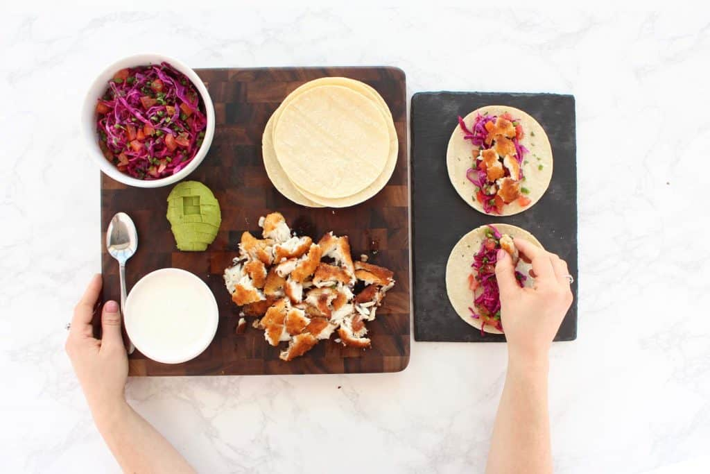 Two hands assembling fish tacos on brown cutting board.