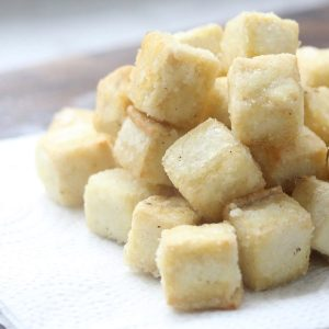 Crispy tofu cubes on paper towel.