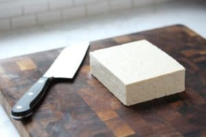 Brick of tofu on cutting board.
