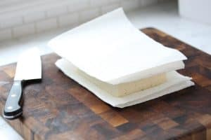 Tofu wrapped in paper towels on cutting board.