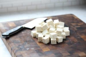 Cubed tofu on cutting board.