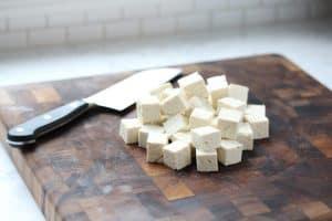 Cubed tofu on cutting board.