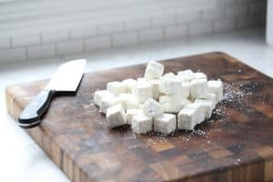 Cubed tofu coated in corn starch on cutting board.