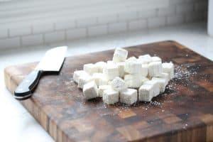 Cubed tofu coated in corn starch on cutting board.