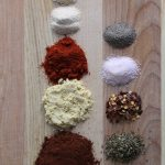 Spices on brown cutting board.
