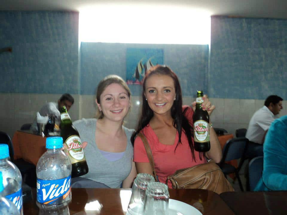 Two women holding beers.
