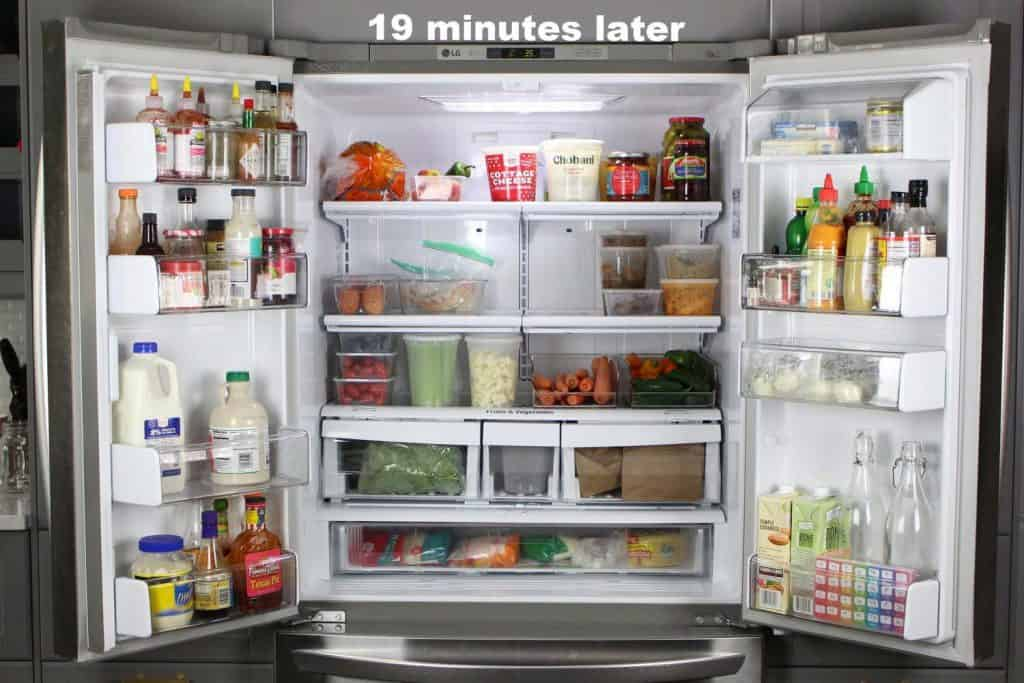 Open double door refrigerator with organized food.