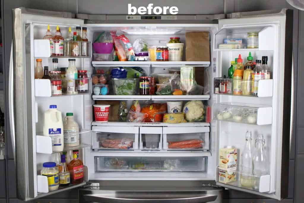 Open double door refrigerator with disorganized food.