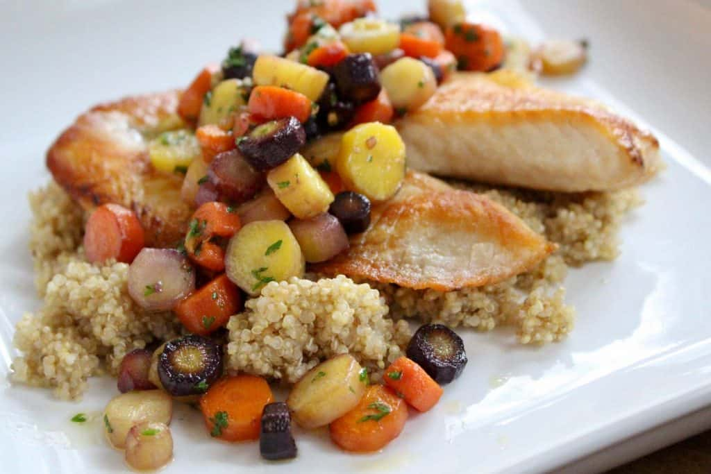Sliced carrots over tilapia and quinoa on white plate.