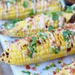 Grilled corn on marble cutting board.