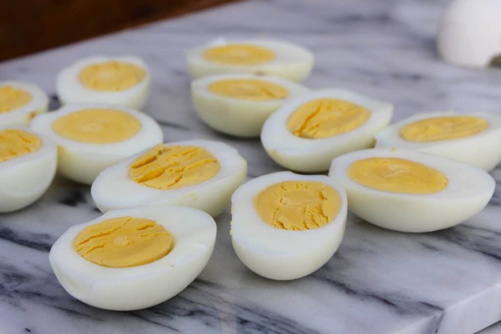 Hard cooked eggs cut in half on marble surface.