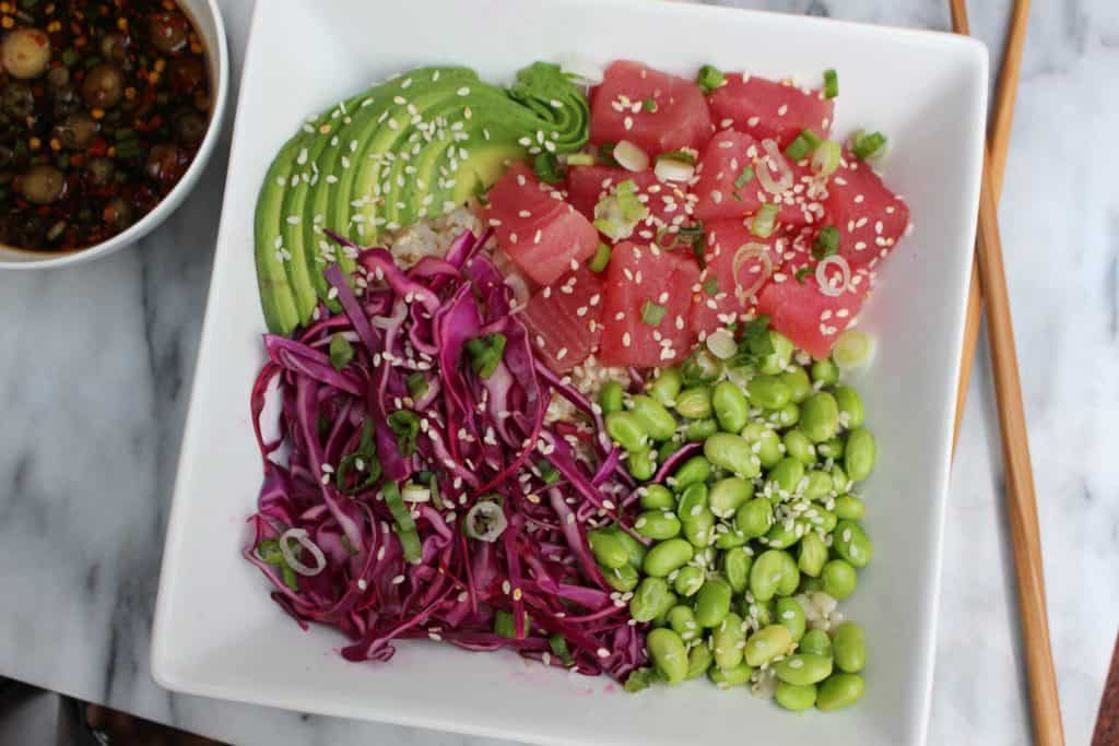 Raw tuna, edamame, avocado and cabbage in white bowl.