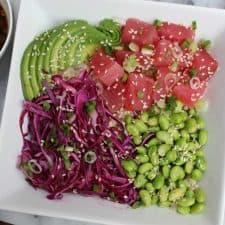Raw tuna, edamame, avocado and cabbage in white bowl.