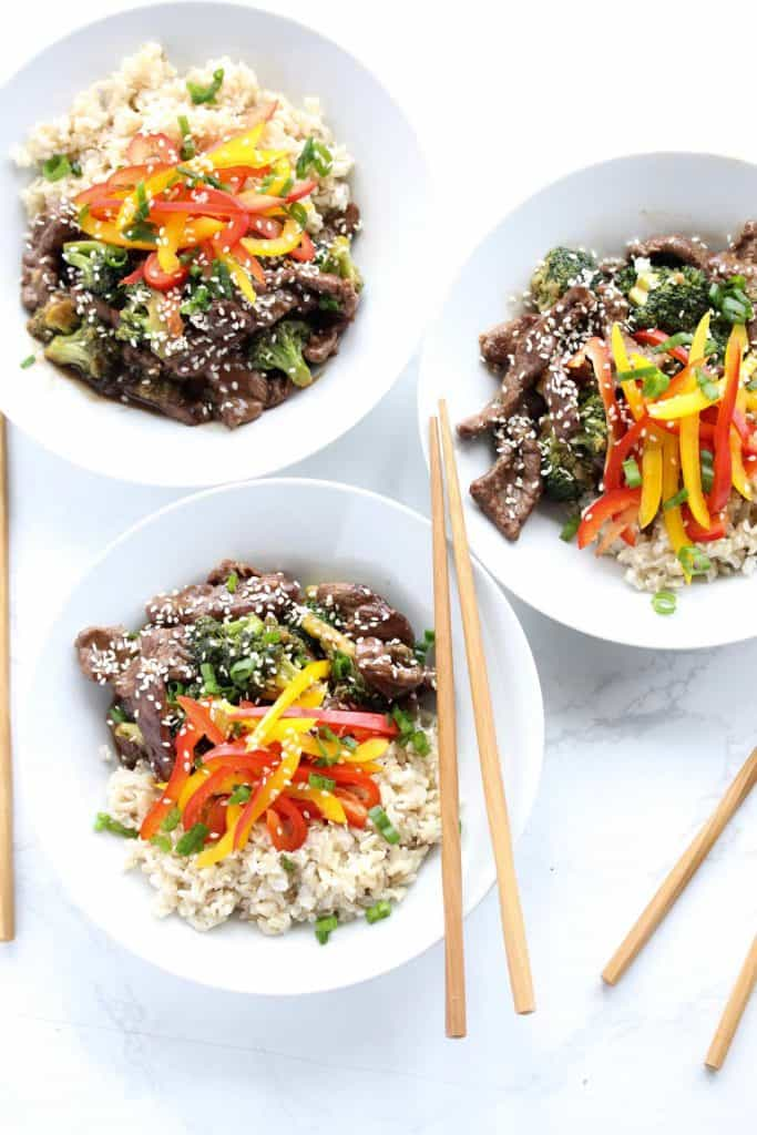 Beef and broccoli stir fry in three white bowls with chopsticks.