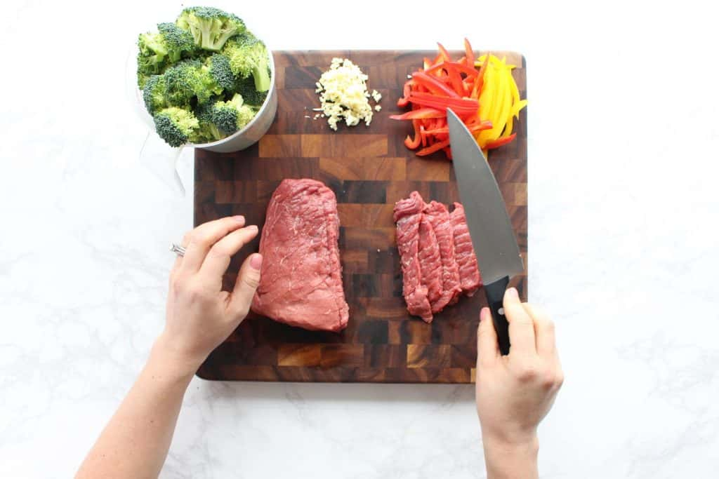 Two hands cutting beef on brown cutting board.