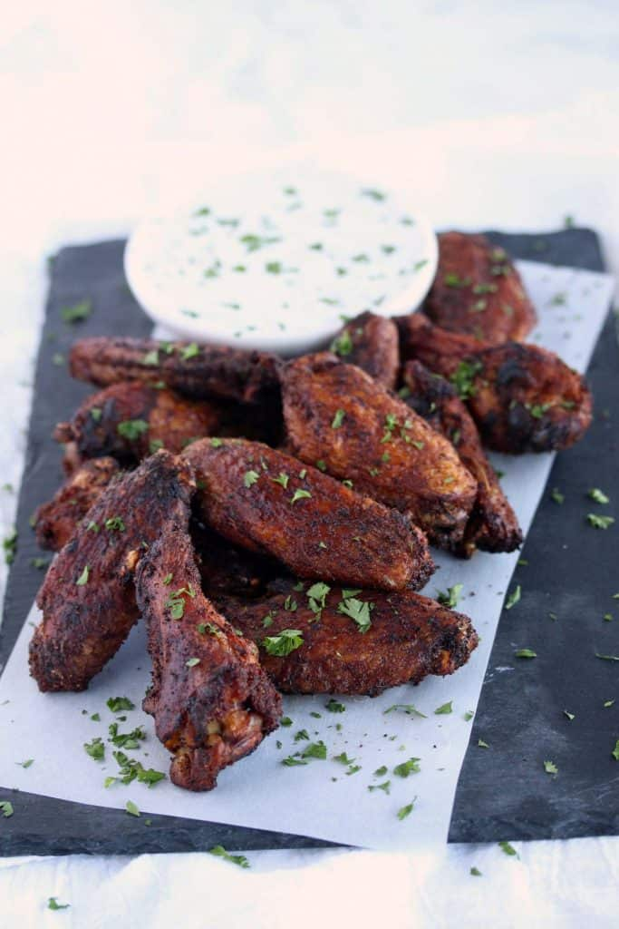 Crispy wings on blue serving platter with dip.