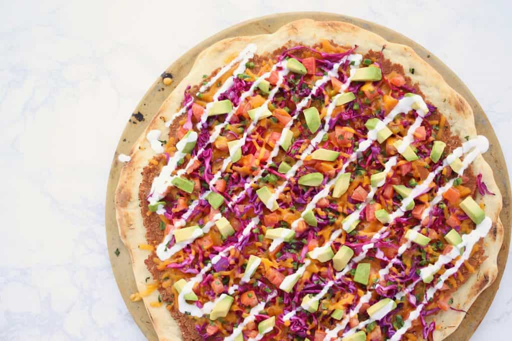 Colorful pizza on white surface.