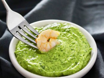 Shrimp on fork dipped in green sauce in white bowl.