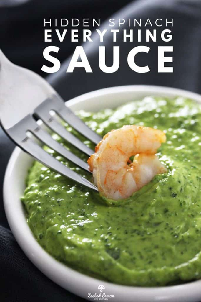 Shrimp on fork dipped in green sauce in white bowl.